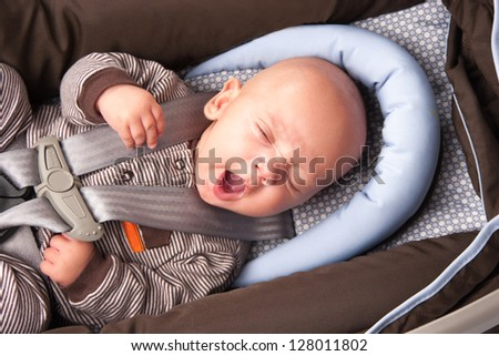 Portrait of a yawning baby Boy In Safety Seat - stock photo
