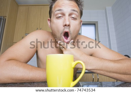 Portrait of a yawning man in the kitchen with a colorful yellow mug of coffee. - stock photo