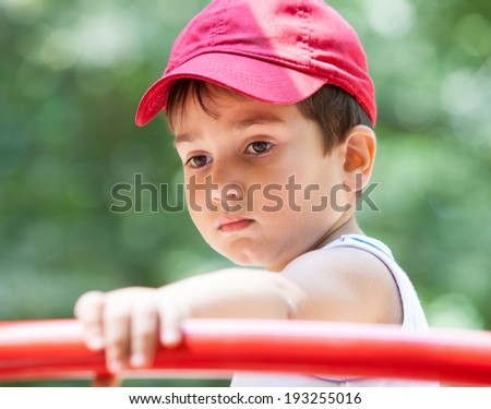 Portrait of a 3-4 years boy playing on the playground. Shallow DOF - stock photo