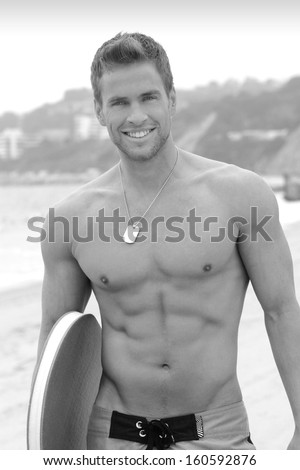 Portrait of a young active muscular man at beach with surfboard - stock photo