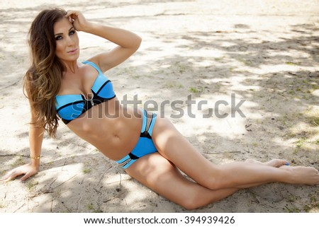 Portrait of a young adult attractive sexy and sensuality beautiful brunette woman in bikini on the beach - stock photo