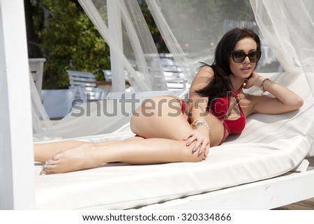 Portrait of a young adult attractive sexy and sensuality pretty beautiful brunette woman in red bikini on the sunbed summer sunlight beach