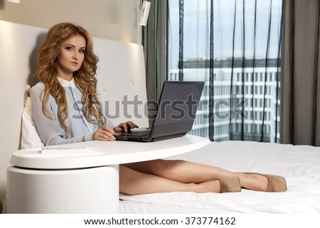 Portrait of a young adult beauty attractive sexy and sensuality happy pretty blonde businesswoman using laptop while lying on bed in hotel bedroom - stock photo