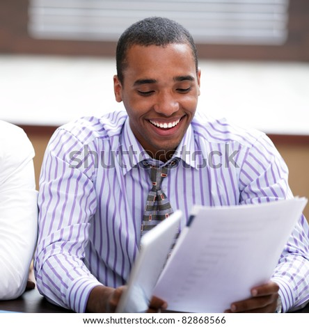 Portrait of a young african-american businessman smiling while working at the meeting - stock photo