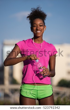 portrait of a young African American girl to run beautiful summer morning on city streets with headphones and a bottle of water