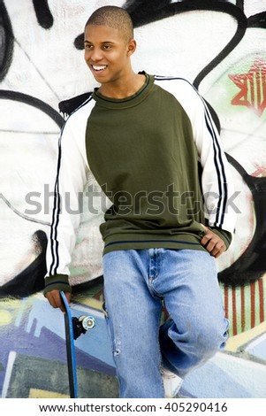 Portrait of a young African American man in front of a graffiti covered wall - stock photo