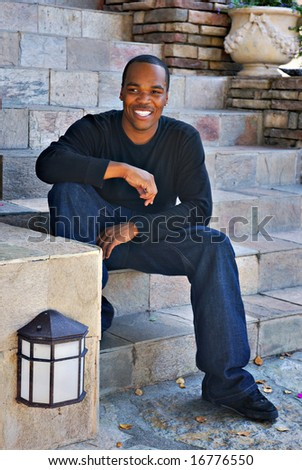 Portrait of a young African American man sitting on rock stairs - stock photo