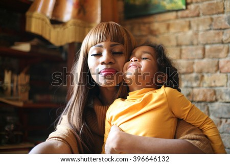 Portrait of a young African American woman and her daughter hugging.  - stock photo