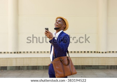 Portrait of a young african businessman walking with a cellphone and bag - stock photo