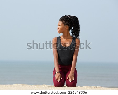 Portrait of a young african woman kneeling outdoors on beach - stock photo