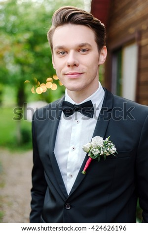 Portrait of a young and attractive groom at a wedding. Outdoor. He is smiling and happy - stock photo