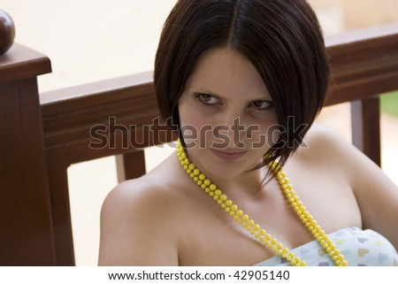 Portrait of a young and beautiful woman sitting on the porch during summertime - stock photo