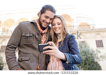 Portrait of a young and fashionable couple taking a picture of themselves while on vacation in a destination city, holding a digital photo camera with their heads together. - stock photo