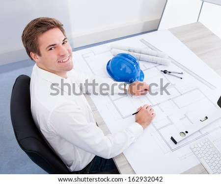 Portrait Of A Young Architect Drawing Plan On Blueprint - stock photo
