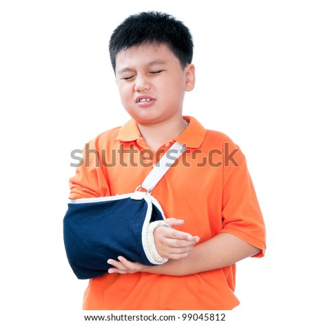 Portrait of a young Asian boy in pain with fractured hand in plaster cast, isolated on white background. - stock photo