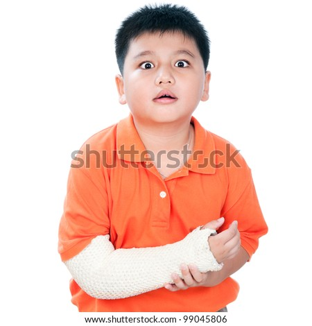 Portrait of a young Asian boy with fractured hand in plaster cast against white background. - stock photo