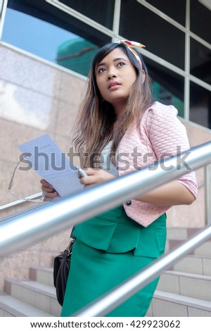 Portrait of a young Asian business woman smiling, reading a letter, walking at an outdoor office environment - stock photo