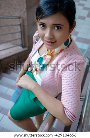 Portrait of a young Asian business woman smiling, walking at an outdoor office environment - stock photo