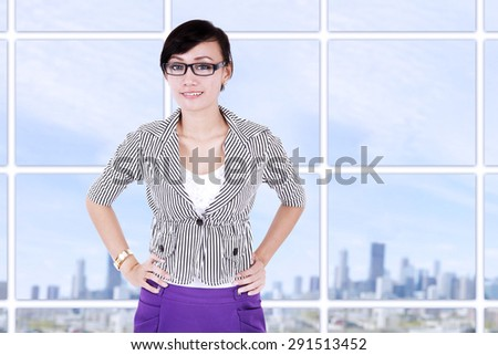 Portrait of a young asian businesswoman smiling at modern office - stock photo