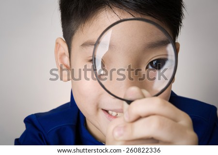 portrait of a young asian child looking through a magnifying glass on gray background