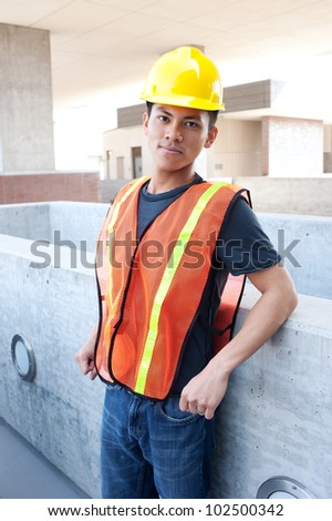 portrait of a young asian construction worker standing outside