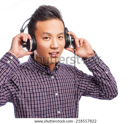 portrait of a young asian man listening to music - stock photo