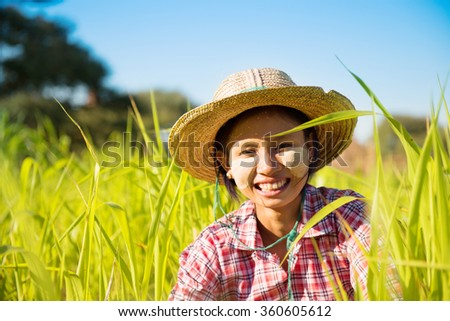 Portrait of a young Asian Myanmar farmer with thanaka powdered face working in the paddy field.