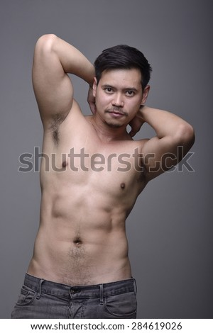 Portrait of a young Asian sexy muscular posing on a white background. - stock photo