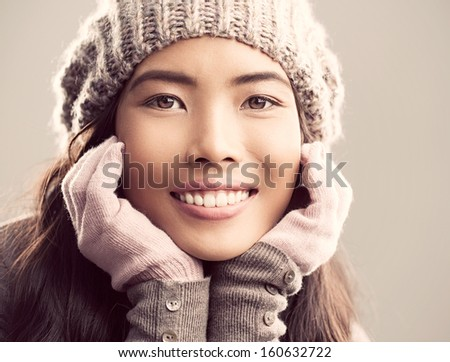 Portrait of a young Asian woman dressed in warm winter clothes. - stock photo