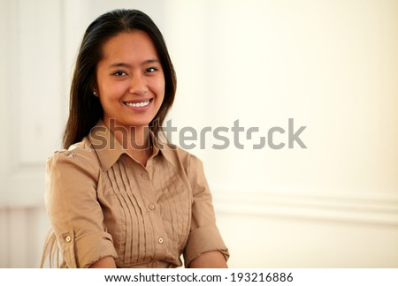 Portrait of a young asiatic woman on brown blouse smiling at you on closeup background - copyspace - stock photo