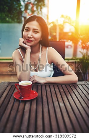 Portrait of a young attractive asian woman enjoys aromatic coffee sitting in a modern cafe on the terrace in the warm summer evening, beautiful female posing with amazing sunset light on background - stock photo