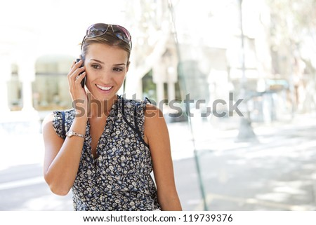 Portrait of a young attractive businesswoman using her smart phone to make a call while standing in a classic city street, smiling during conversation. - stock photo