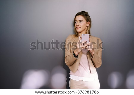 Portrait of a young attractive businesswoman with blonde hair using smart-phone on a gray background with copy space area for your text o design. - stock photo