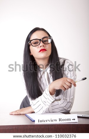 Portrait of a young attractive female secretary with a sign interview room.