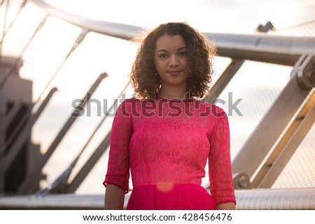 Portrait of a young, attractive girl in pink dress; fashion and beauty - stock photo
