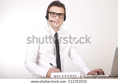Portrait of a young attractive male receptionist smiling. - stock photo