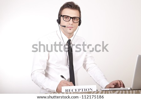 Portrait of a young attractive male receptionist working.