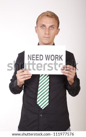 Portrait of a young attractive man holding a sign need work. - stock photo