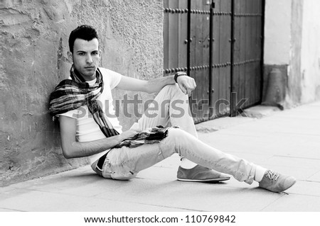 Portrait of a young attractive man sitting on the floor of the street - stock photo