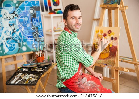 Portrait of a young attractive man working on a painting of flowers and enjoying his work as an artist - stock photo