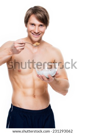 Portrait of a young attractive muscular man eating flakes with milk - isolated on white background. - stock photo