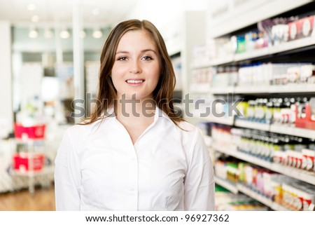 Portrait of a young attractive pharmacist looking at the camera in a pharmacy - stock photo
