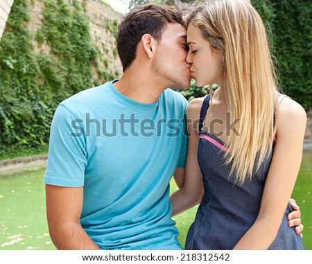 Portrait of a young attractive tourist romantic couple kissing and enjoying a day out sightseeing and traveling together, outdoors. Romance lovers and relationships. - stock photo