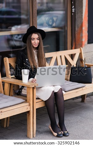 Portrait of a young attractive woman connected to internet via a portable laptop computer, pretty female freelancer using net-book for distance work while sitting on a bench outdoors in coffee shop  - stock photo