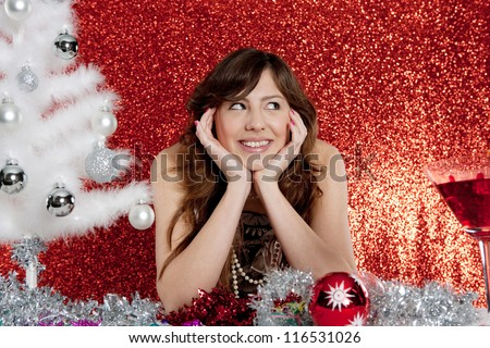 Portrait of a young attractive woman decorating a small christmas tree sitting at a table in front of a red glitter background.