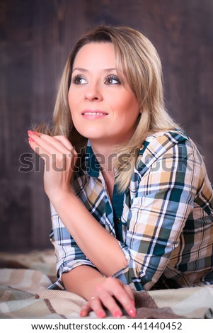 Portrait of a young attractive woman lying on a plaid blanket, close-up portrait, studio shooting - stock photo