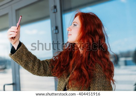 Portrait of a young attractive woman making selfie photo on smartphone for Instagram on a shopping mall background - stock photo