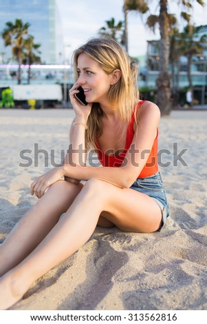 Portrait of a young attractive woman talking on mobile phone while sitting on the beach, pretty hipster girl having smart phone conversation outdoors, caucasian blonde female talking on her cellphone - stock photo