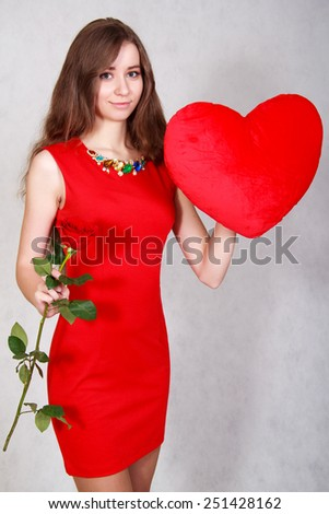 Portrait of a young attractive woman with a heart-shaped pillow and a rose over grey background - stock photo
