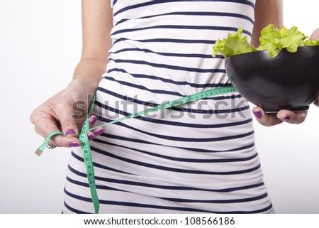 Portrait of a young attractive woman with a measuring tape. - stock photo